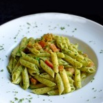 Penne pasta with shredded parmesan cheese and pesto sauce